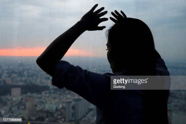 Silhouette of woman looking through the window. Ho Chi Minh City. Vietnam.