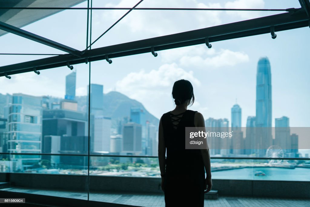 Silhouette of woman looking through window at prosperous skyline of Hong Kong : Stock Photo