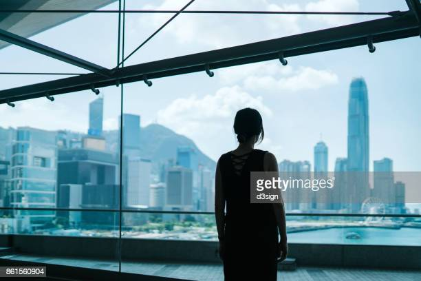 Silhouette of woman looking through window at prosperous skyline of Hong Kong