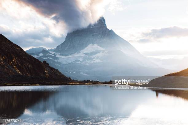 silhouette of woman meeting beautiful sunset above mountain lake and matterhorn - reflection lake stock pictures, royalty-free photos & images