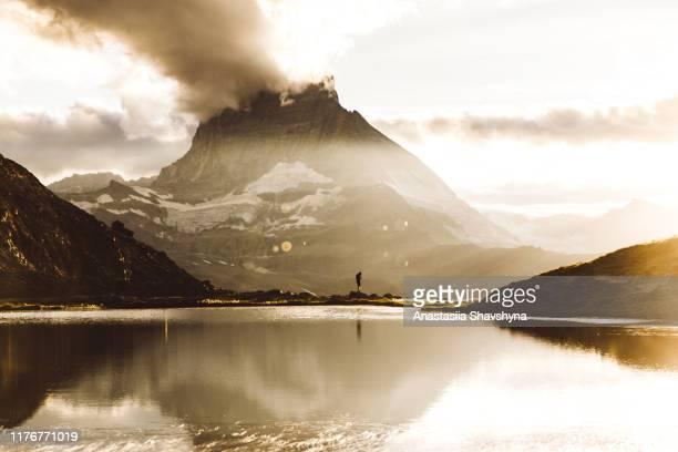 silhouette of woman meeting beautiful sunset above mountain lake and matterhorn - lago reflection foto e immagini stock