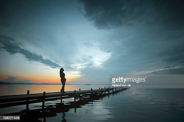 Silhouette der Frau am Seeufer Bootssteg mit majestätischen Sonnenuntergang Wolkengebilde