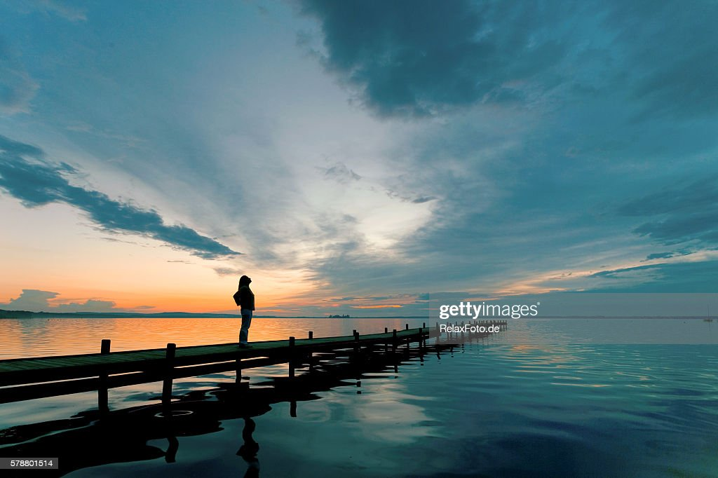 Silhouette of Woman on Lakeside Jetty with majestic Sunset Cloudscape : Stock Photo