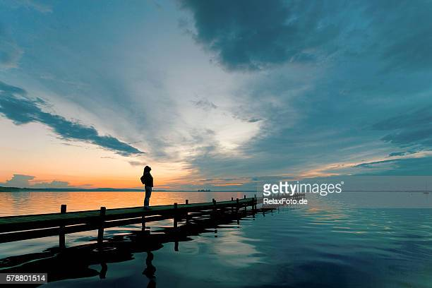 silhouette of woman on lakeside jetty with majestic sunset cloudscape - avondschemering stockfoto's en -beelden
