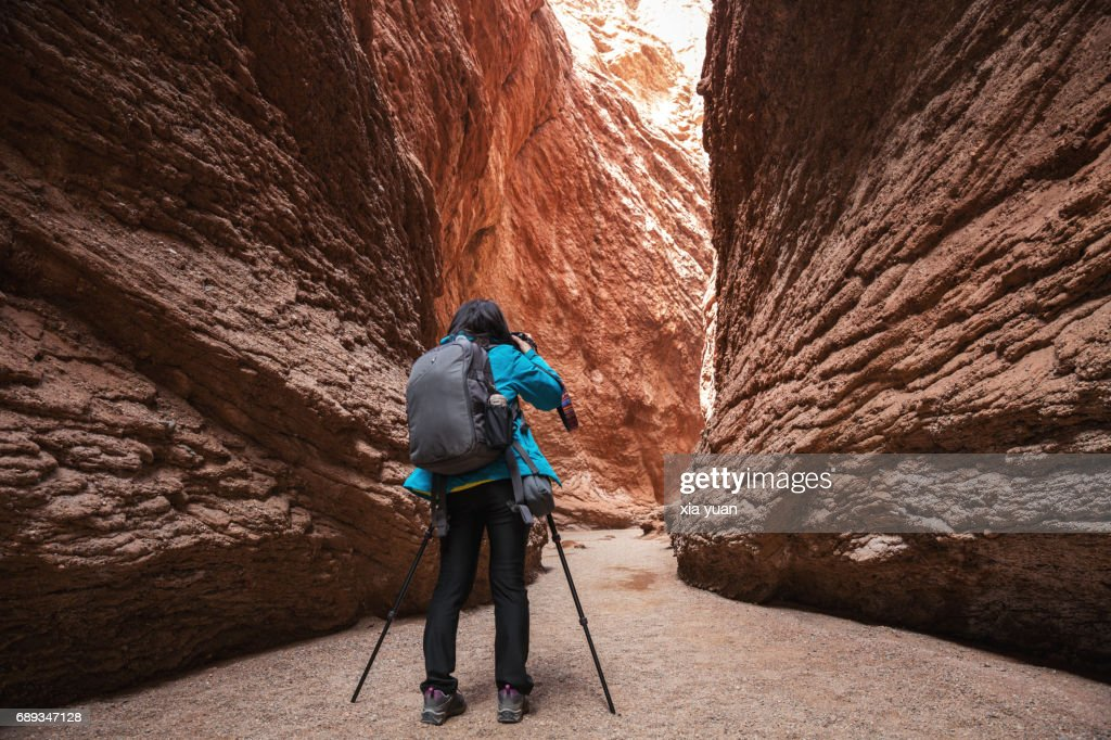 Silhouette of woman photographer taking pictures with tripod in Tianshan Mysterious Grand Canyon,Kuqa,China : Stock Photo