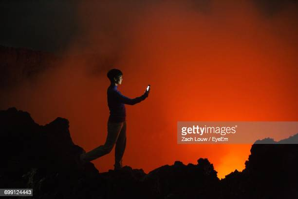 Silhouette Of Woman Photographing Volcanic Eruption