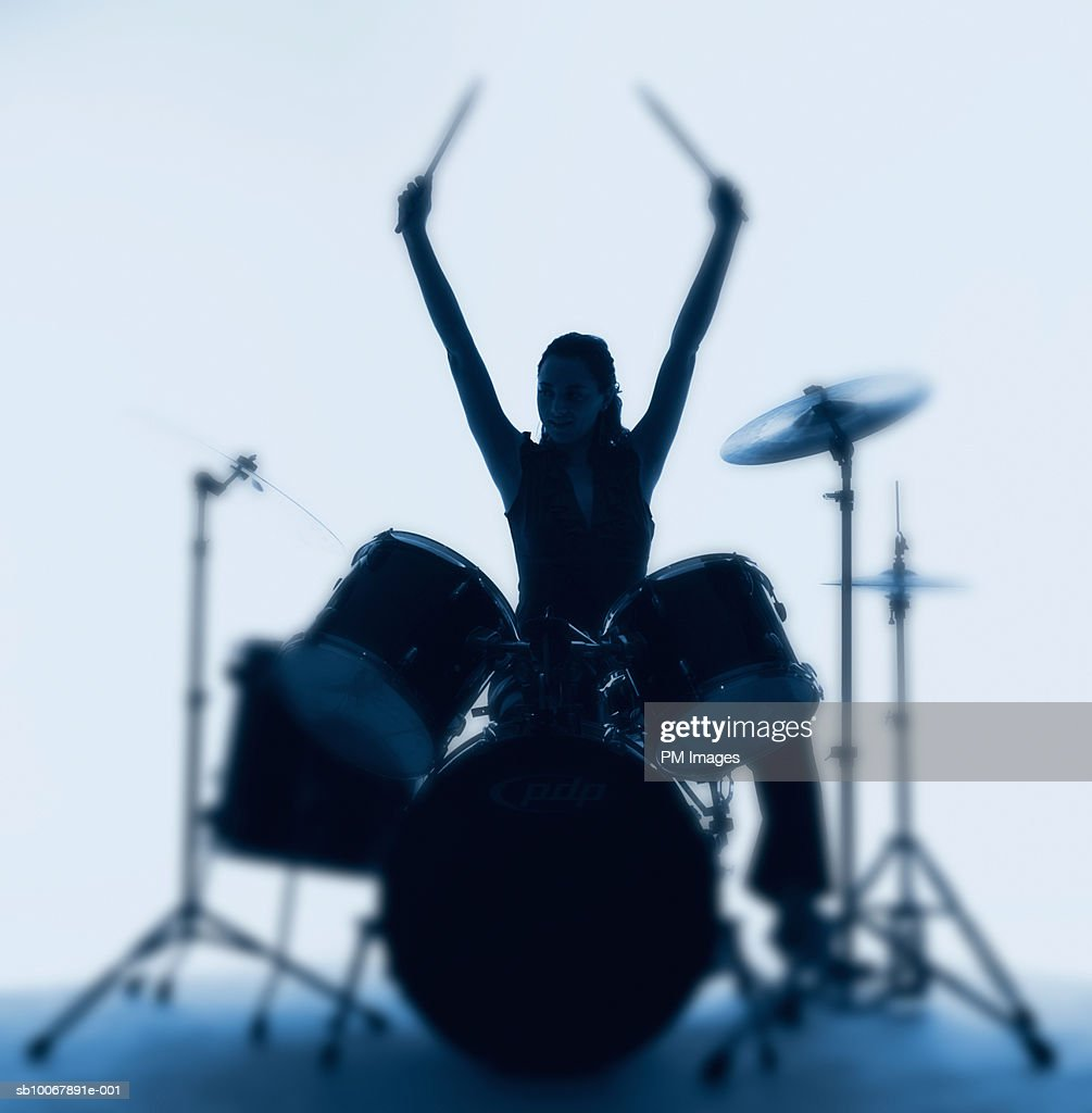 Silhouette of woman playing drums : Stock Photo