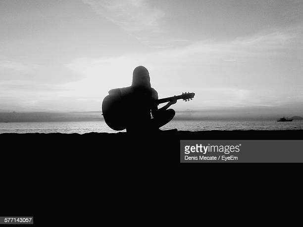 Silhouette Of Woman Playing Guitar On Beach