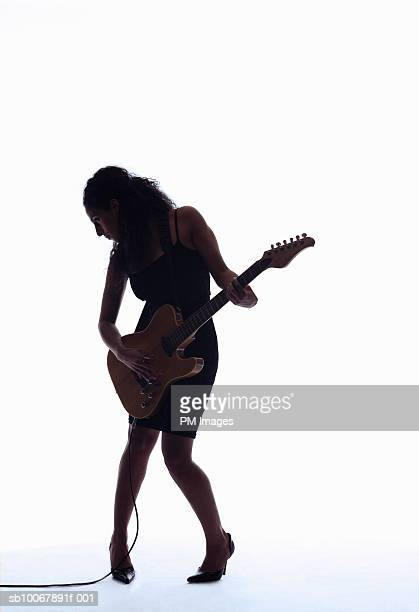 Silhouette of woman playing guitar
