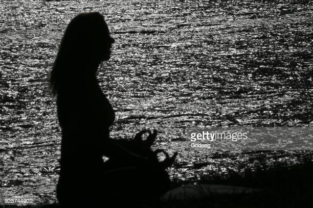 Silhouette of woman practicing yoga at sunset Lotus position French Alps France
