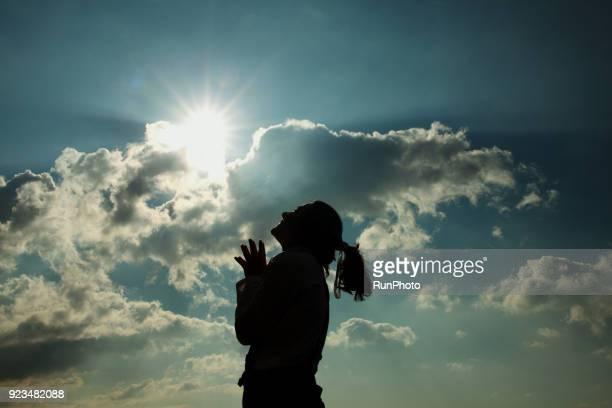 silhouette of woman praying at sunset - 祈る ストックフォトと画像