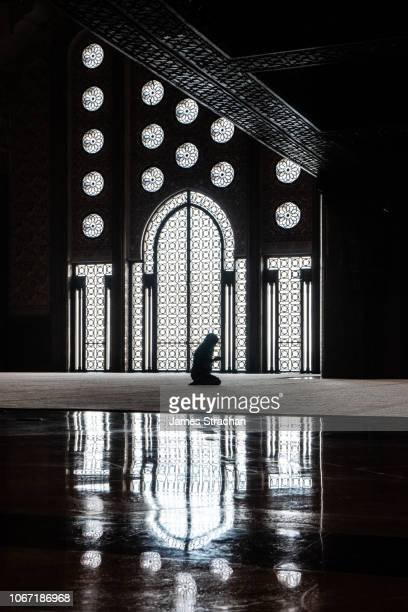silhouette of woman praying in prayer hall of hassan ii mosque (2nd largest in the world outside mecca), opened in 1993, against intricately patterned grilled doors and windows with reflections in marble floor, casablanca, morocco - religion stock pictures, royalty-free photos & images
