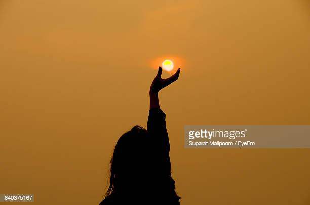 silhouette of woman reaching toward sun at sunset - opportunity stock pictures, royalty-free photos & images