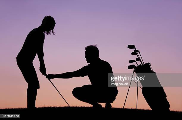silhouette of woman recieving golf lesson from instructor - driving range stock photos and pictures
