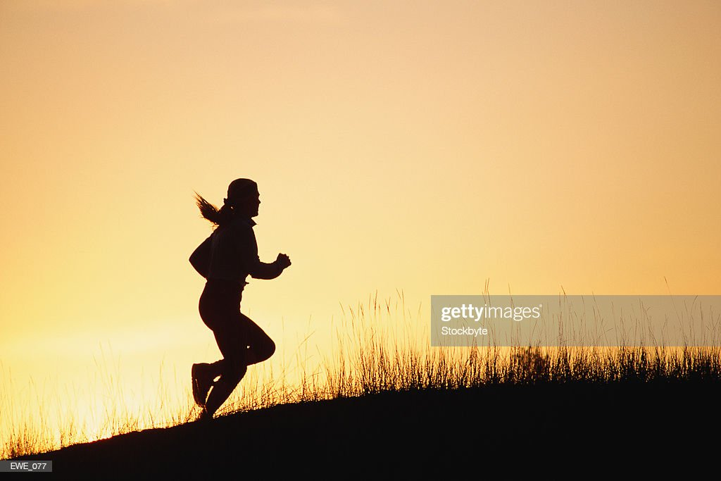Silhouette of woman running up hill : Stock Photo