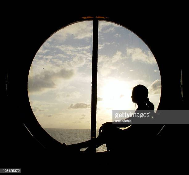 silhouette of woman sitting in ship's porthole window - porthole stock photos and pictures
