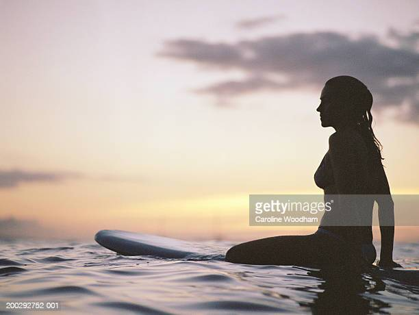 Silhouette of woman sitting on surfboard in ocean, sunset