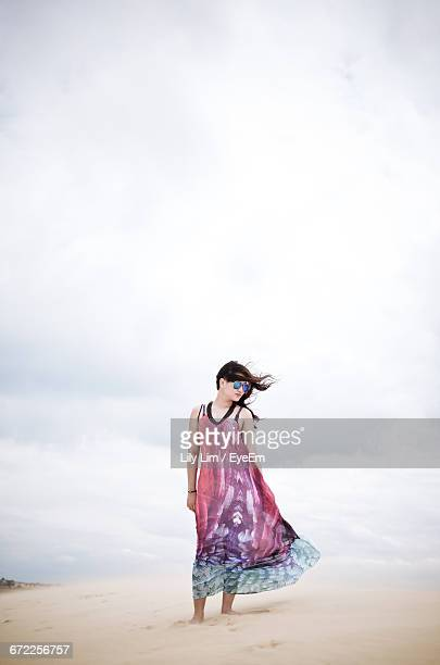 Silhouette Of Woman Standing Against Cloudy Sky At The Beach