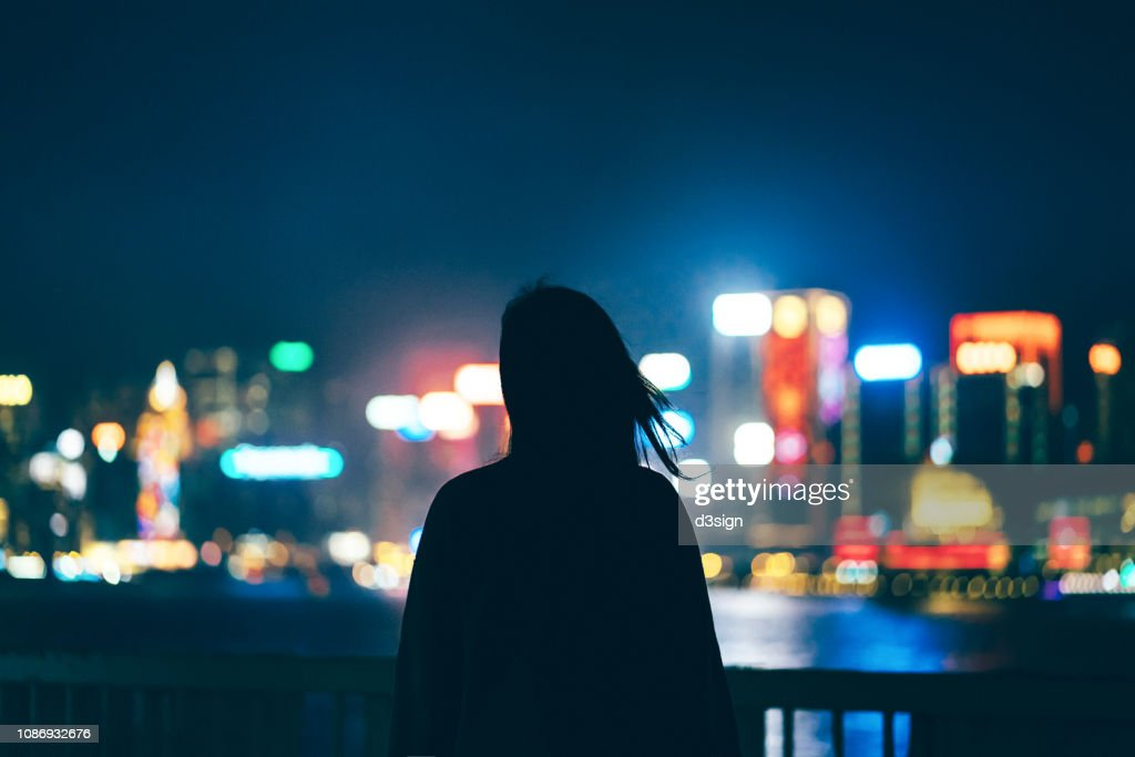 Silhouette of woman standing against illuminated and multi-coloured cityscape at night : Stock Photo