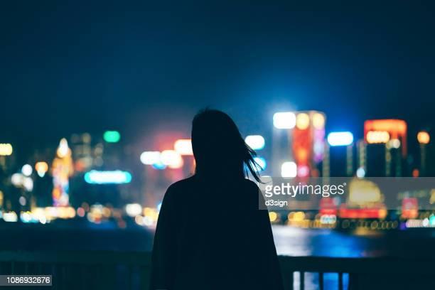 silhouette of woman standing against illuminated and multi-coloured cityscape at night - contraluz fotografías e imágenes de stock