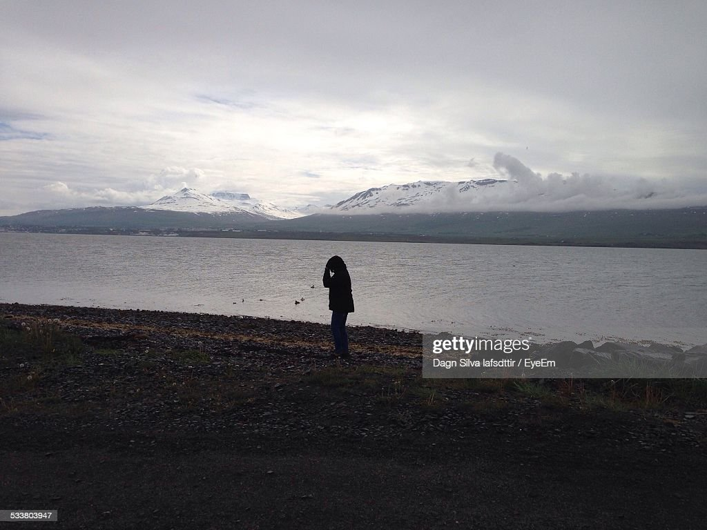 Silhouette Of Woman Standing, Bay And Mountains In Background : Foto stock