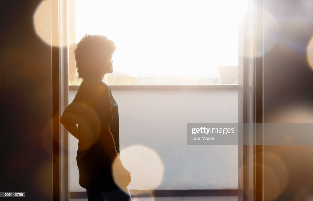 silhouette of woman standing by window : Stock-Foto