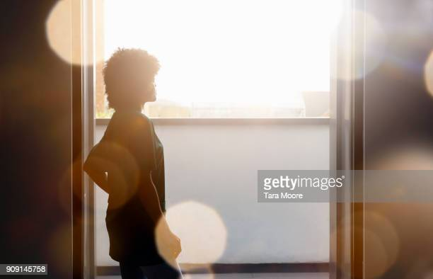 silhouette of woman standing by window - projection stock pictures, royalty-free photos & images