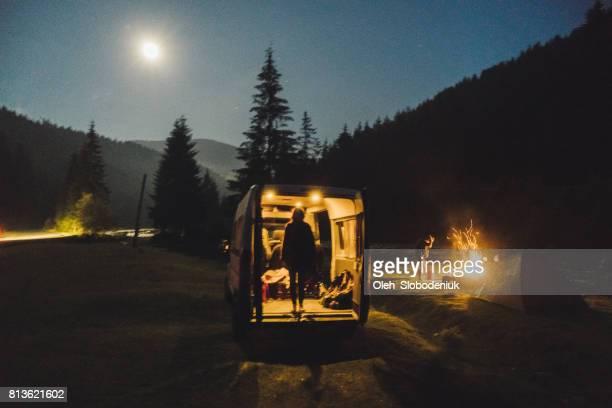 Silhouette der Frau, die in der van in der Nacht in der Nähe des Campingplatzes