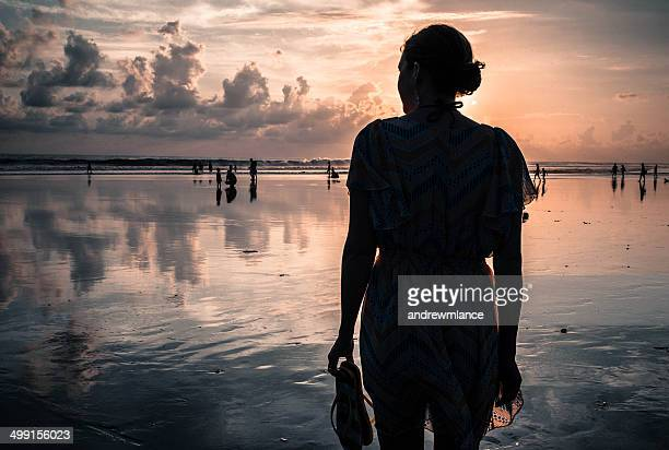 Silhouette of woman standing on beach at sunset, Legian, bali, Indonesia