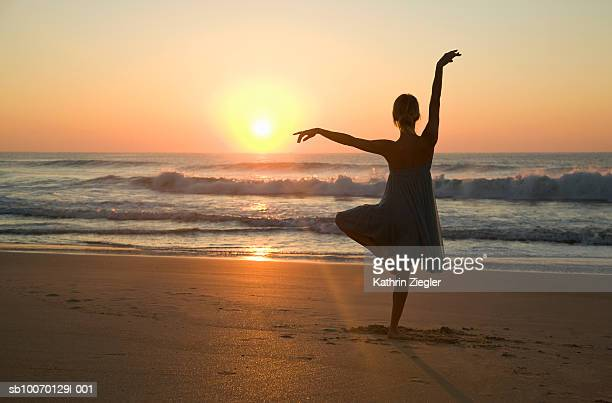 Silhouette of woman standing on one leg and arms up on beach, rear view