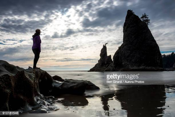silhouette of woman standing on rock on beach and looking at rock formation, rialto beach, la push, washington state, usa - rialto beach stock photos and pictures