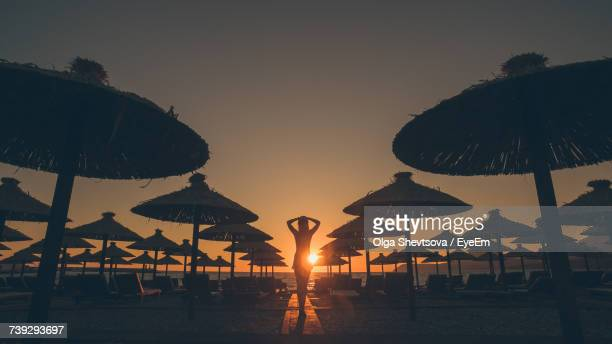 Silhouette Of Woman Standing With Head In Hands By Lounge Chairs And Parasols At Beach During Sunset
