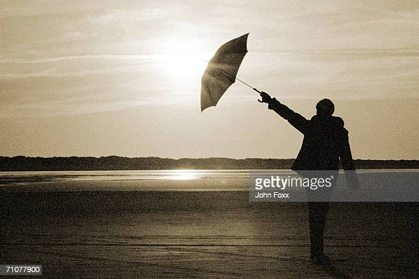 Silhouette of woman standing with umbrella (B&W)