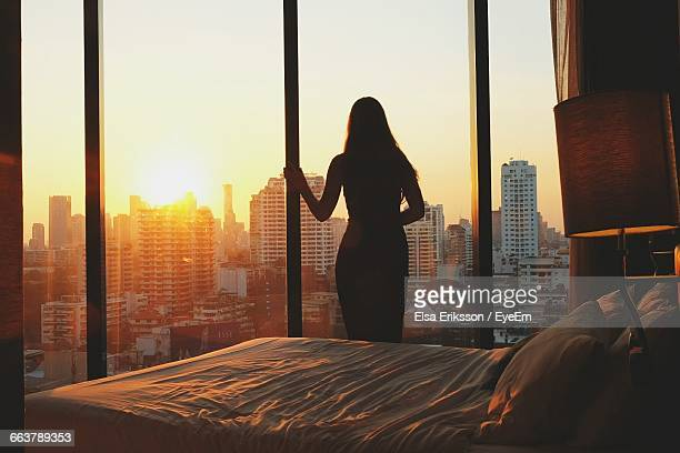 silhouette of woman staring out at beautiful world - morgen stock-fotos und bilder