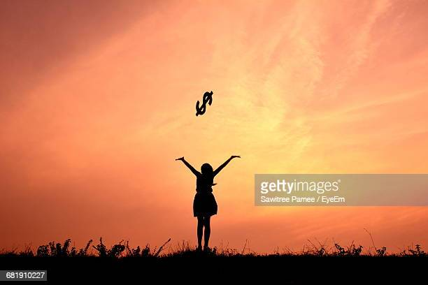Silhouette Of Woman Throwing Dollar Sign Symbol At Sunset