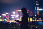 Silhouette of woman using tablet device in city