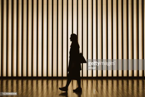 silhouette of woman walking in front of striped illuminated wall - art foto e immagini stock