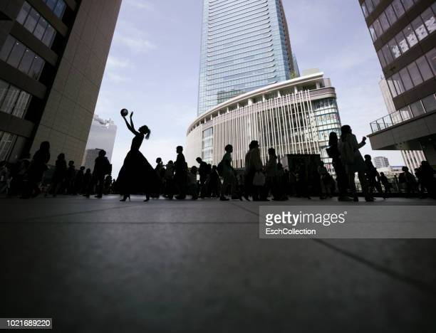 Silhouette of woman with ball outside Osaka Station in Japan