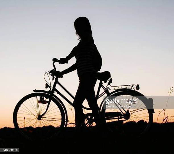 silhouette of woman with bicycle against sky - pedal stock pictures, royalty-free photos & images