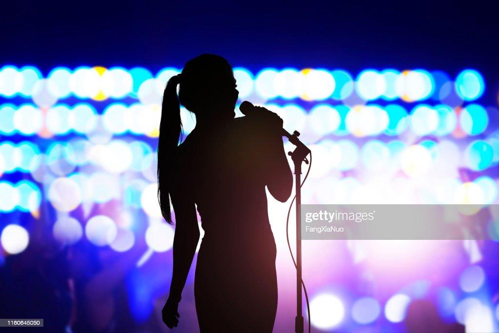 Silhueta da mulher com o microfone que canta no estágio do concerto na frente da multidão : Foto de stock
