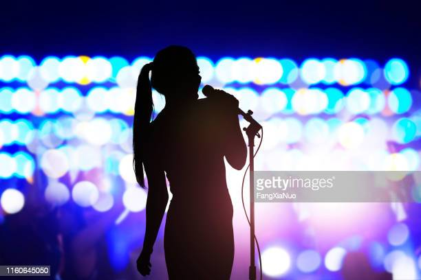 silhouette of woman with microphone singing on concert stage in front of crowd - singer stock pictures, royalty-free photos & images
