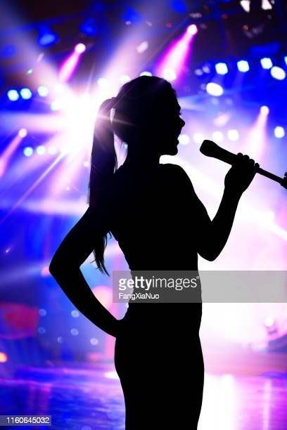 silhouette of woman with microphone singing on concert stage - lead singer stock pictures, royalty-free photos & images