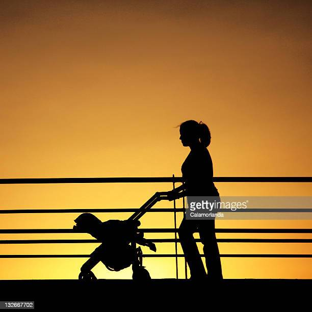 Silhouette of woman with pram