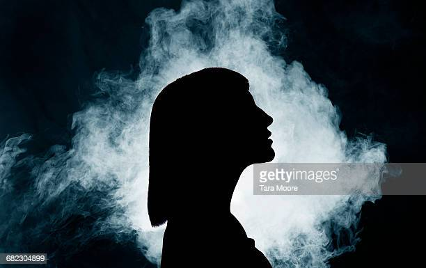 silhouette of woman with smoke - back lit stock pictures, royalty-free photos & images