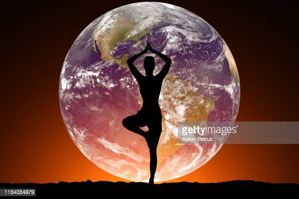 silhouette of women doing yoga on the background of the planet earth. - human brain stock pictures, royalty-free photos & images