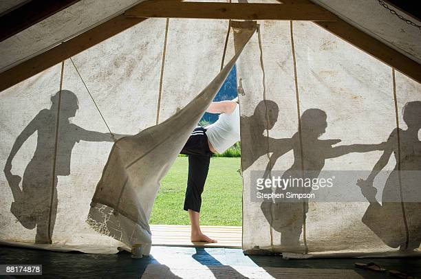 Silhouette of women doing yoga outside of tent