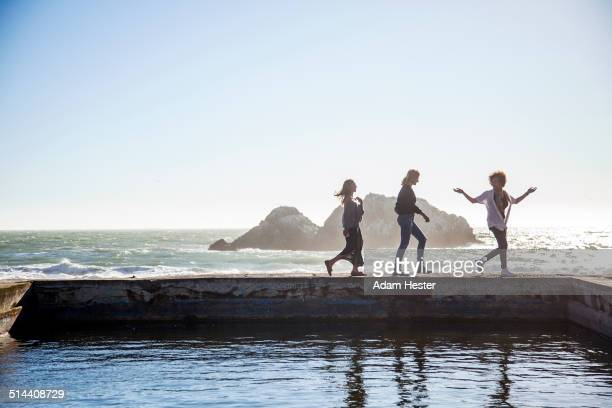 Silhouette of women walking on pool on coastline