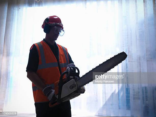 Silhouette of worker with a chainsaw