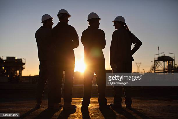 silhouette of workers at oil refinery - oil refinery stock pictures, royalty-free photos & images