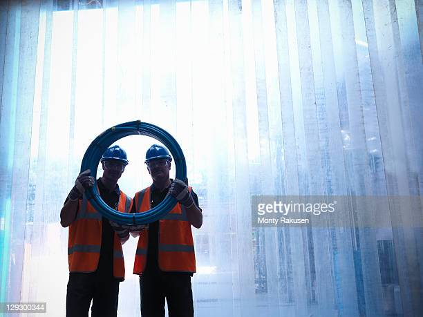 Silhouette of workers holding blue water pipes
